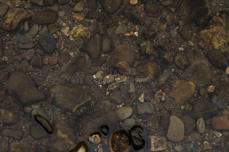 Piedras en el río fotografiado desde arriba de/agua de río clara y foto colorida de las piedras de piedras en el río claro /Backg fotos de archivo