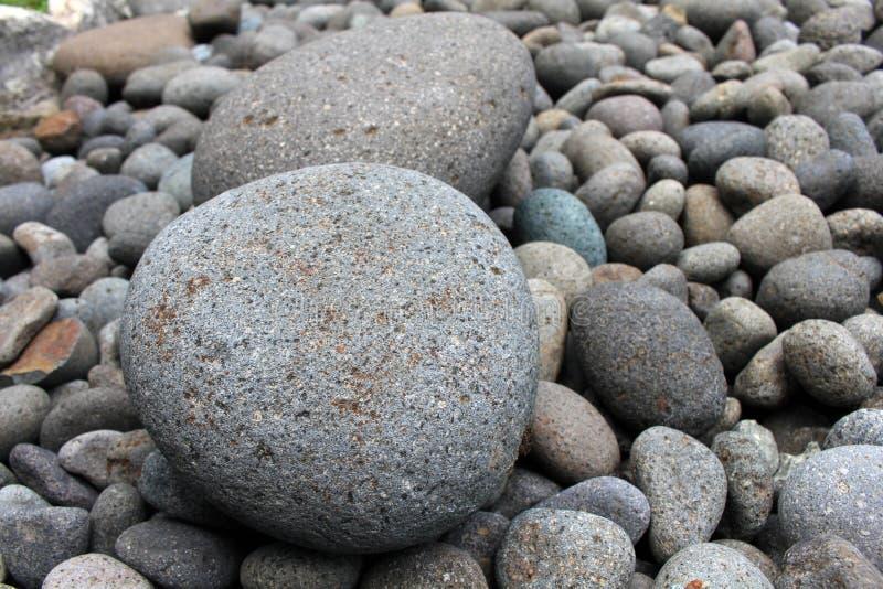 Piedras grandes entre guijarros más pequeños, en el jardín fotos de archivo libres de regalías