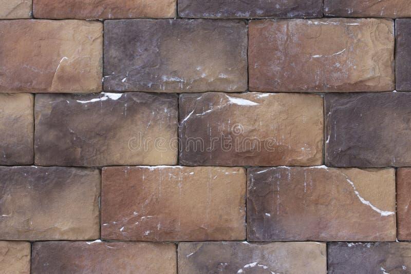 Piedras marrones marrones hermosas de los ladrillos con la nieve, estructura de la textura del fondo Material para la construcció fotografía de archivo