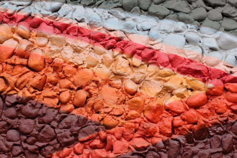Piedras multicoloras La pared se pinta en diversos colores en estilo de la textura Fondo del Grunge fotos de archivo