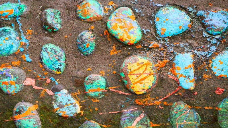 Piedras multicoloras y pescados creativos hechos de piedra La pintura se pinta en diversos colores en estilo de la textura Backgr imagenes de archivo