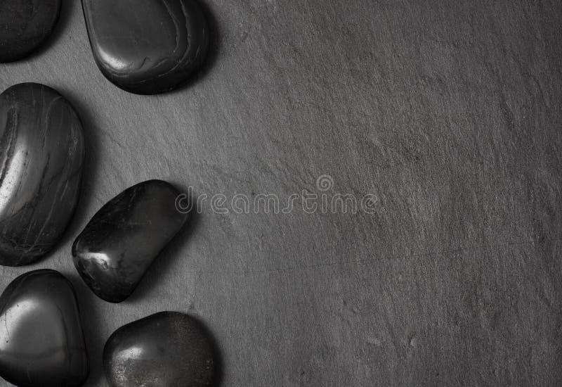 Piedras negras del masaje de la lava en fondo oscuro fotografía de archivo libre de regalías