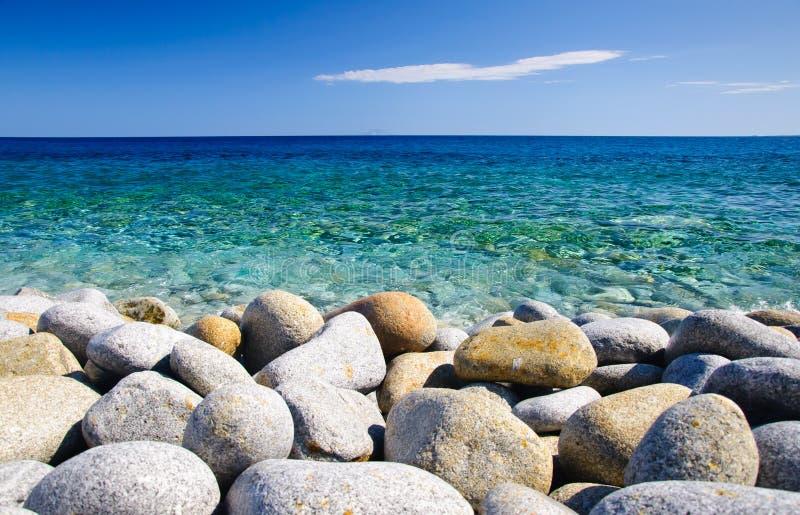 Piedras redondas y mar claro fotos de archivo