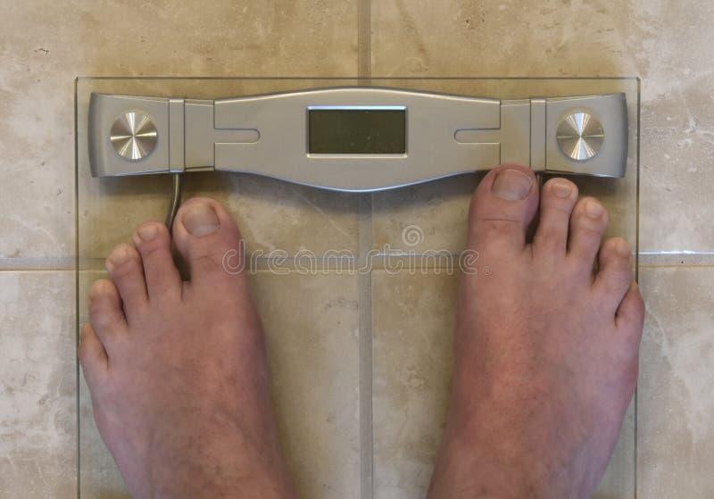 Pieds adultes supérieurs sur l'échelle de salle de bains image libre de droits