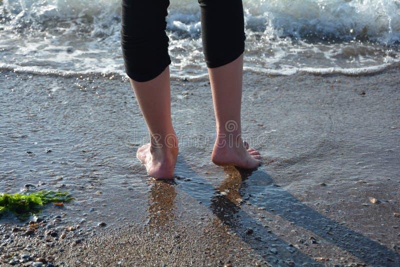 Pieds avant une vague sur la plage sablonneuse photos libres de droits