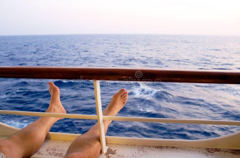 Pieds détendant par le balcon du bateau de croisière des Caraïbes photographie stock