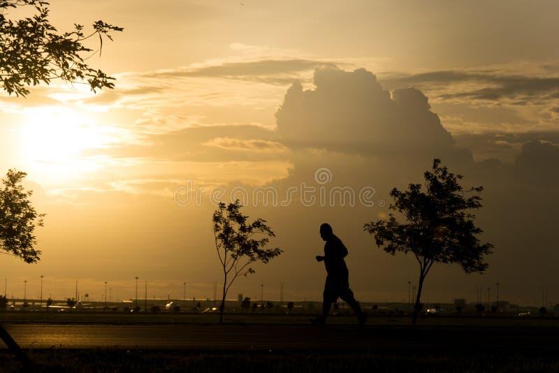 Pieds d'athlète de turbine fonctionnant sur la route lever de soleil j de silhouette de forme physique photos libres de droits