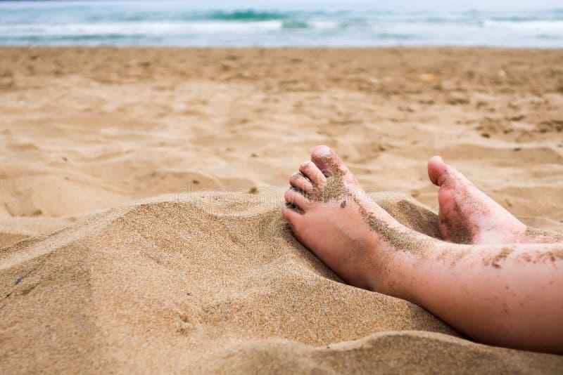 Pieds d'enfant dans le sable sur une plage images stock