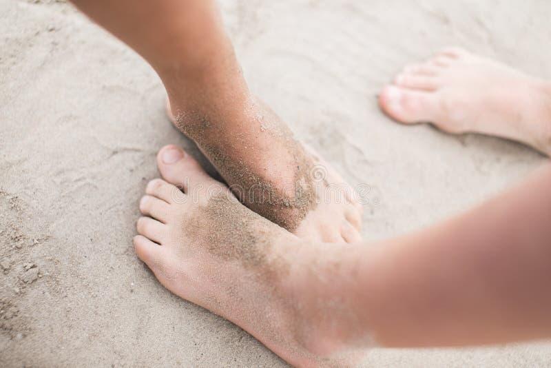 Pieds d'enfant en bas âge sur le sable à la plage photos libres de droits