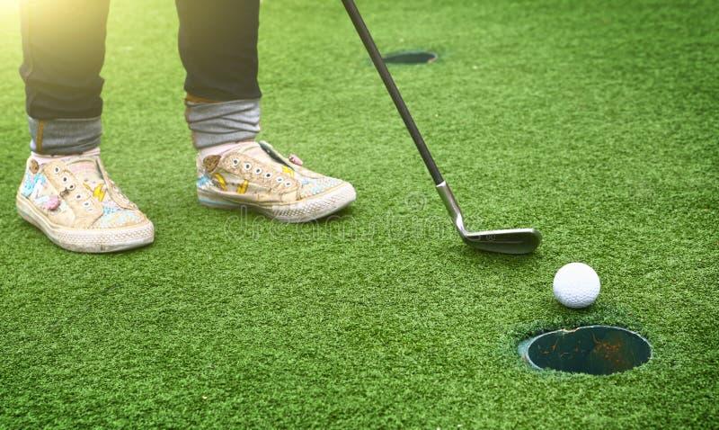 Pieds d'enfants avec le club et la boule de golf allant au trou images stock