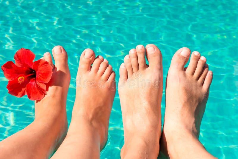 Pieds d'un jeune couple par la piscine photos stock