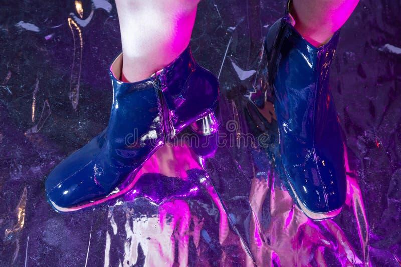Pieds d'une femme blanche dans les bottes bleues avec les lumières colorées image stock