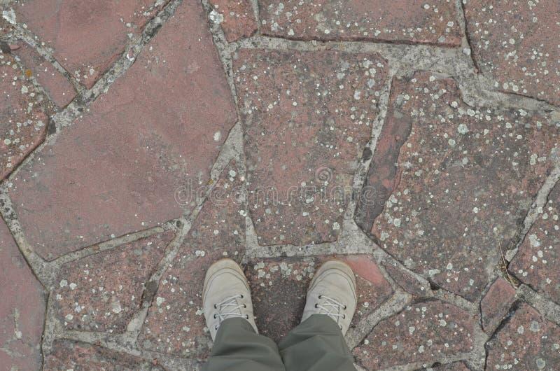 Pieds dans des chaussures de toile blanches se tenant sur le trottoir superficiel par les agents de pierres image stock
