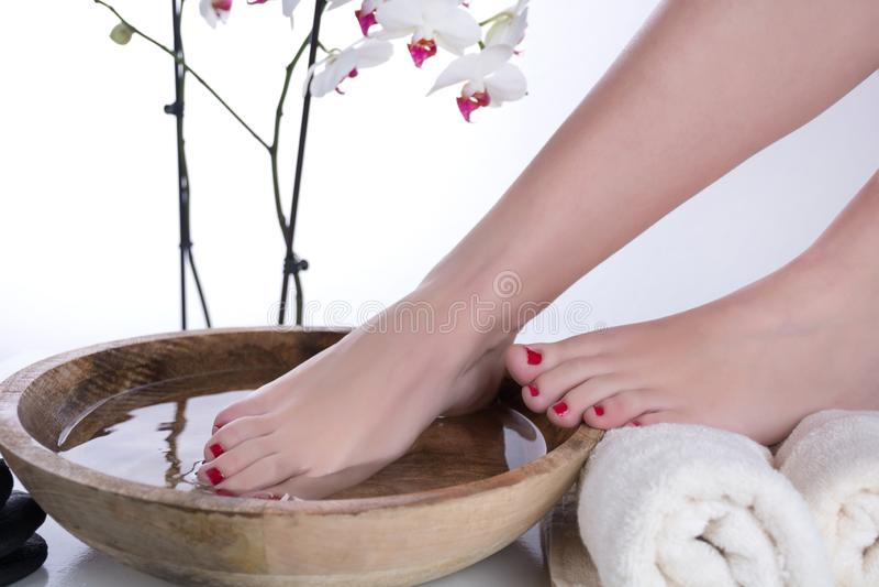 Pieds dans la cuvette en bois avec la fleur de l'eau et de serviette et blanche d'orchidée photos stock