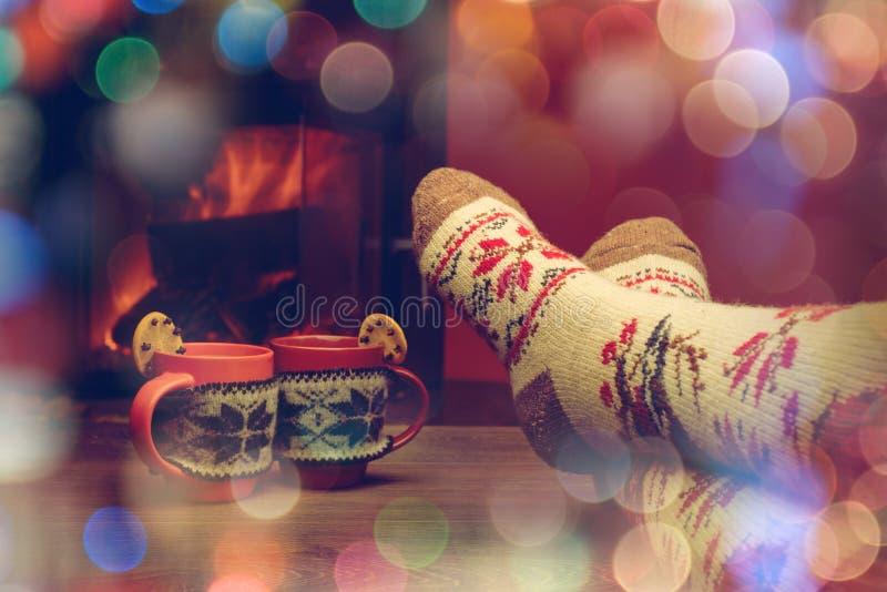 Pieds dans les chaussettes de laine par la cheminée de Noël détend le femme photographie stock libre de droits