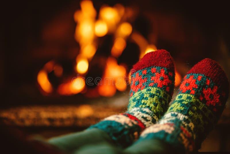 Pieds dans les chaussettes de laine par la cheminée La femme détend par fi chaud images stock