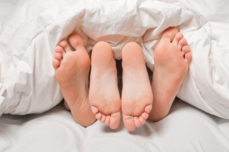 Pieds dans un lit image libre de droits