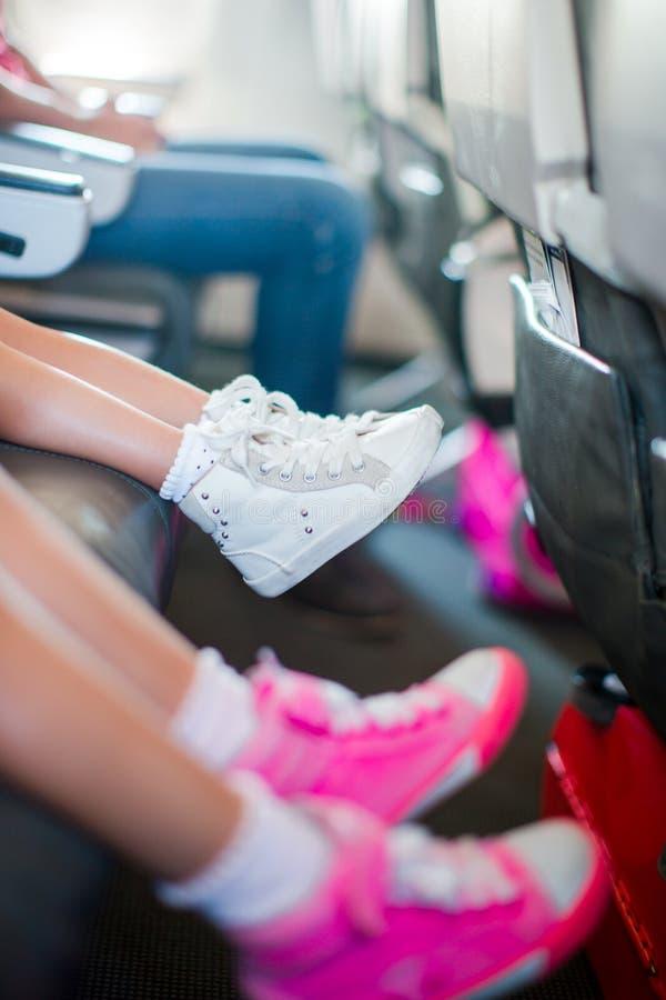 Pieds de bébé dans des espadrilles sur le siège dans les petites filles adorables d'avions marchant dehors dans le domaine de fle image libre de droits