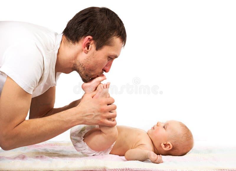 Pieds de baiser de jeune père caucasien de son fils de bébé photo stock