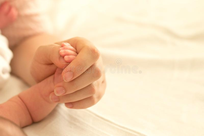 Pieds de chéri dans des mains de mère Maman et son enfant Concept de la famille Belle image conceptuelle de maternité photo stock