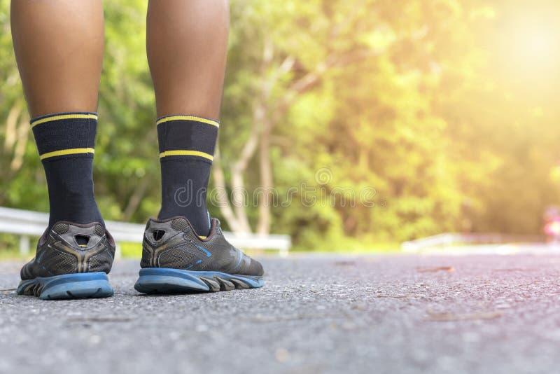 Pieds de coureur d'homme sur la route au foyer mou de bien-être de séance d'entraînement de parc et fin de foyer sur la chaussure photos stock