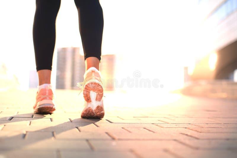 Pieds de coureur fonctionnant sur le plan rapproché de route sur la chaussure, extérieure au coucher du soleil ou au lever de sol image libre de droits