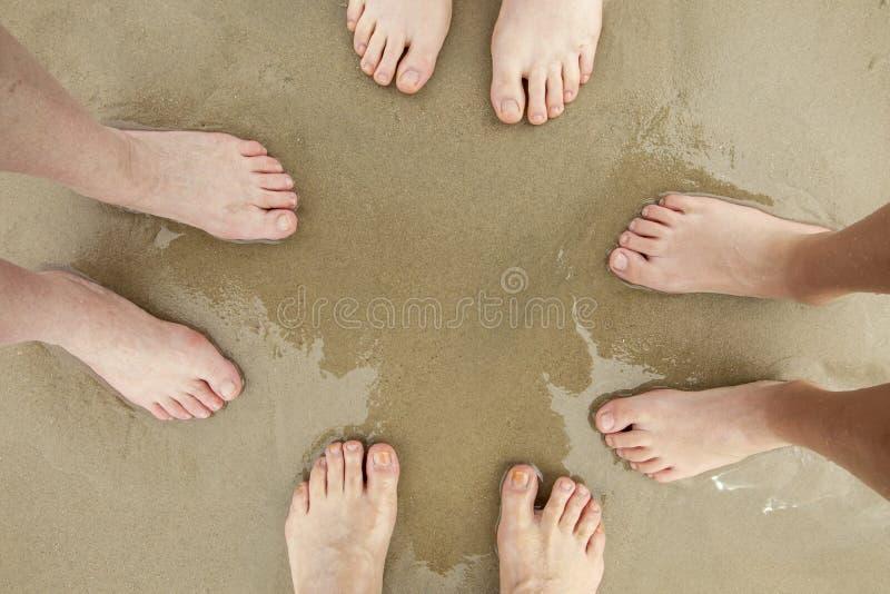 Pieds de famille à la plage sablonneuse images libres de droits