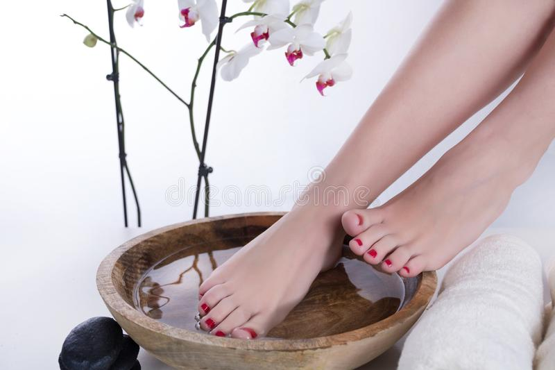 Pieds de femme à la procédure de pédicurie de station thermale Pieds dans la cuvette en bois avec la fleur de l'eau et de serviet photo stock