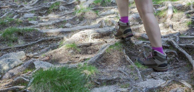 Pieds de femme avec la hausse de bottes de montagne photos stock