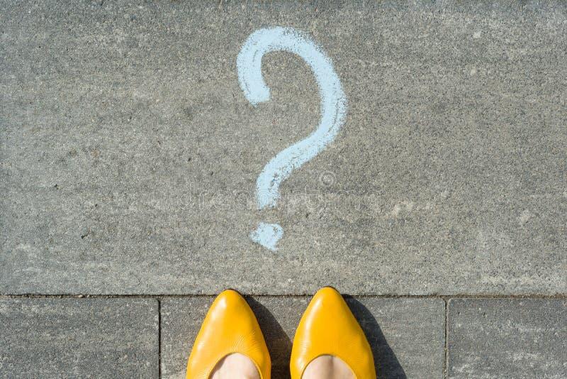 Pieds de femme avec le point d'interrogation devant ses jambes peintes sur l'asphalte photo stock