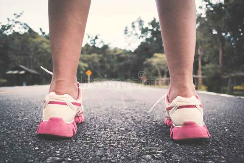 Pieds de femme courant sur la route pour la santé photos libres de droits