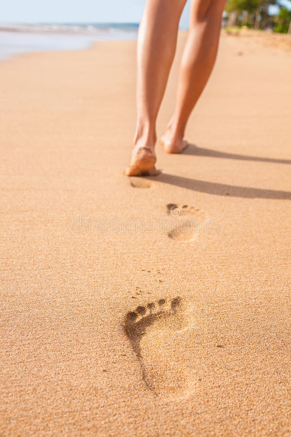 Pieds de femme d'empreintes de pas de sable de plage marchant nu-pieds images stock