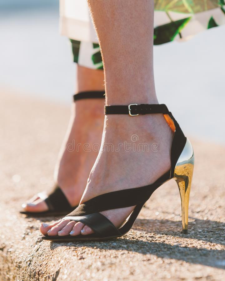 Pieds de femme dans des chaussures d'?t? de talons hauts image stock