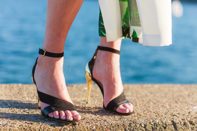 Pieds de femme dans des chaussures de talons hauts sur la jetée de mer photographie stock
