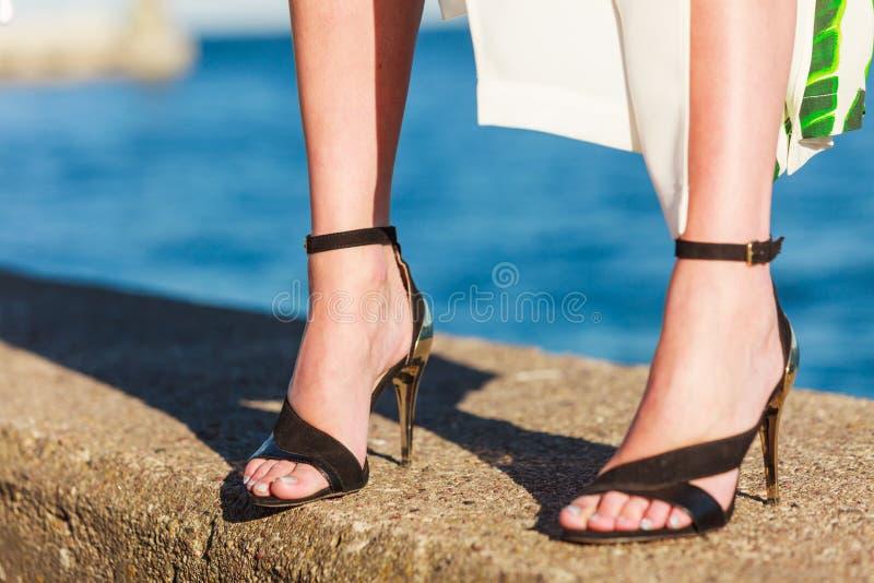 Pieds de femme dans des chaussures de talons hauts sur la jet?e de mer photographie stock