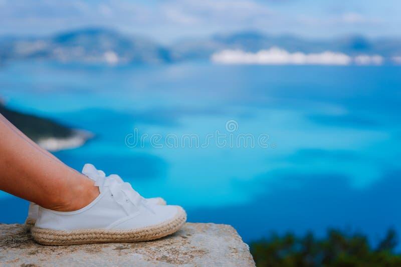 Pieds de femme portant les espadrilles blanches devant le beau paysage marin Jeune femme drôle et heureuse de mode des vacances R images stock
