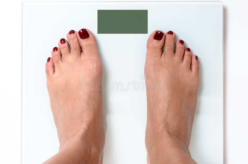 Pieds de femme sur des échelles de poids photographie stock
