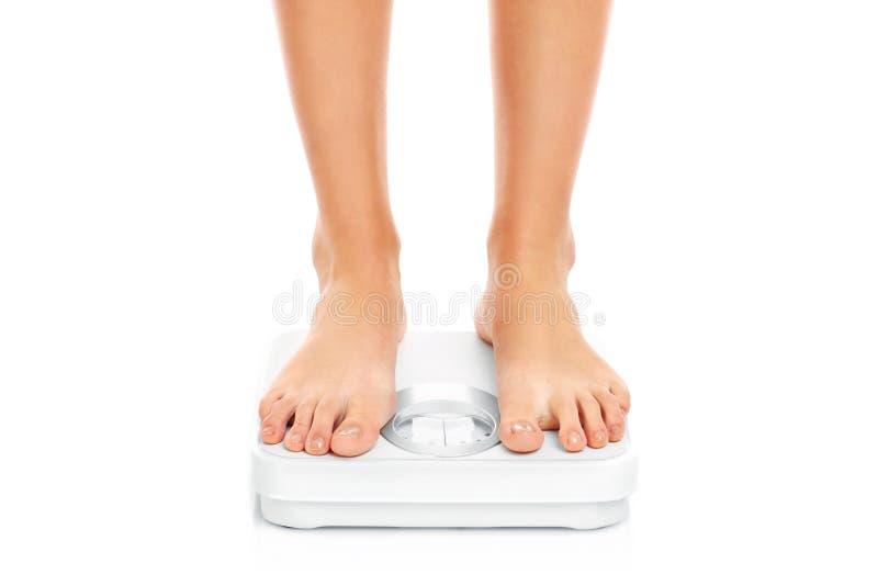 Pieds de femme sur des échelles de salle de bains photo stock