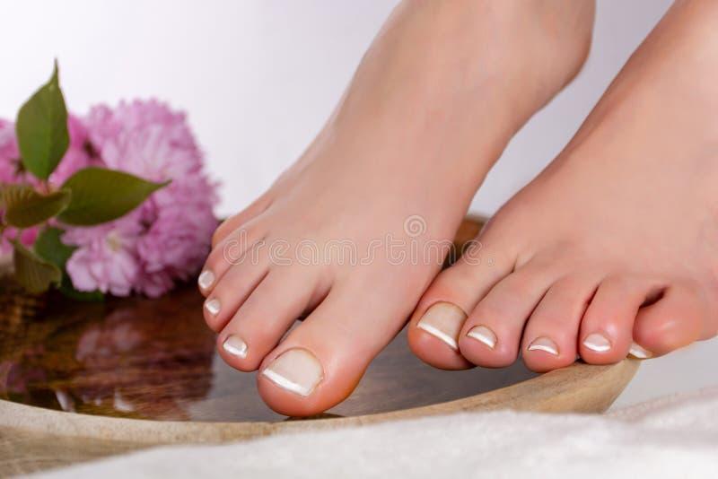 Pieds de fille avec la manucure française blanche sur la cuvette en bois avec la fleur et la serviette décoratives roses dans la  photos stock
