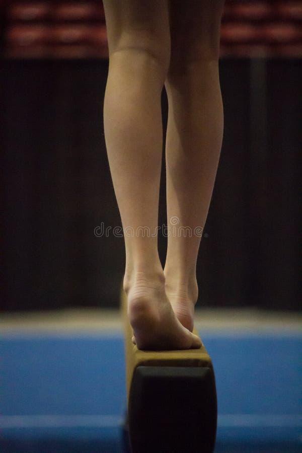 Pieds de filles sur le faisceau d'équilibre photographie stock