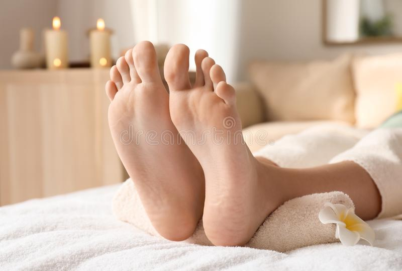 Pieds de jeune femme se trouvant sur la table de massage dans le salon de station thermale images libres de droits
