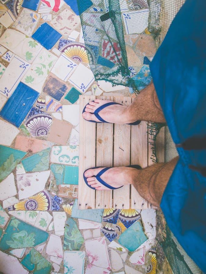 Pieds de jeune homme sur le plancher de trencadis avec des bascules électroniques et des vêtements de bain images libres de droits