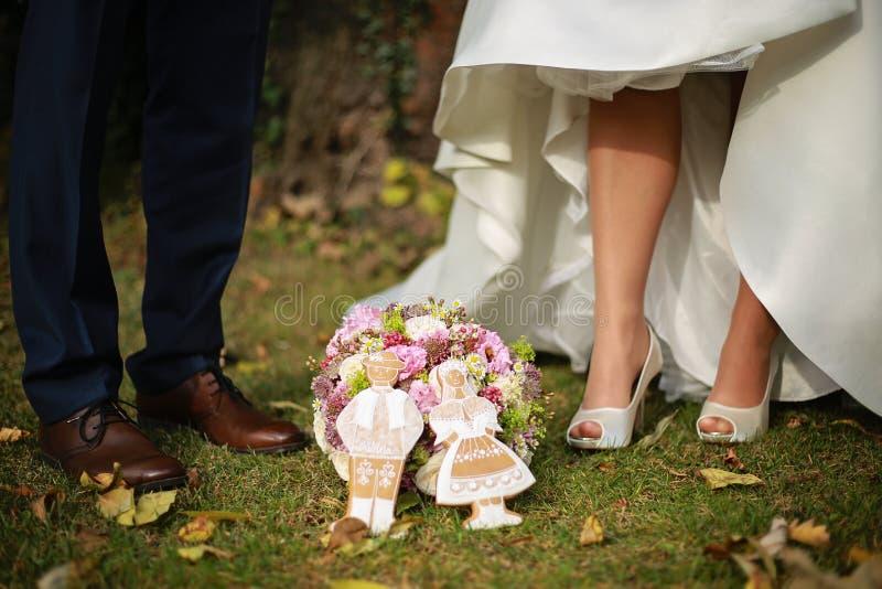Pieds de jeunes mariés avec le bouquet de mariage et le gingerbrea de mariage image stock