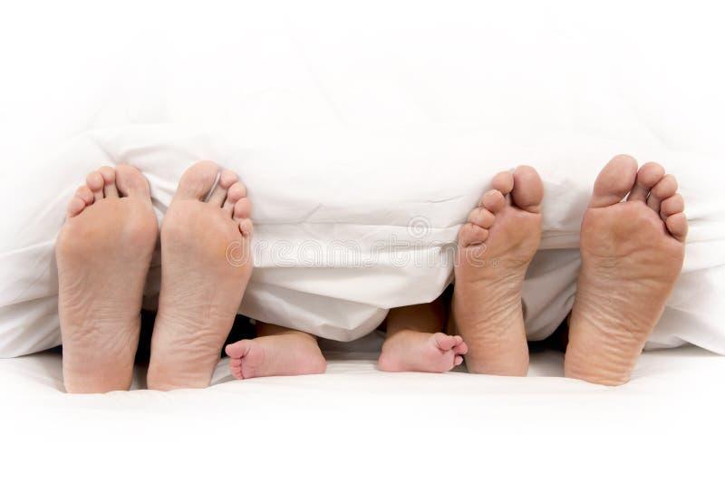 Pieds de père et de bébé de mère sous la couverture image stock
