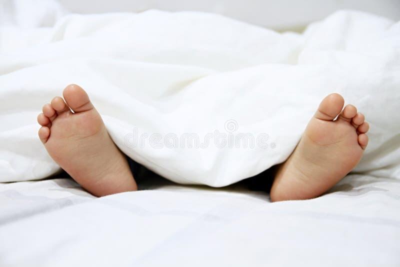 Pieds de petits garçons dans le lit photographie stock