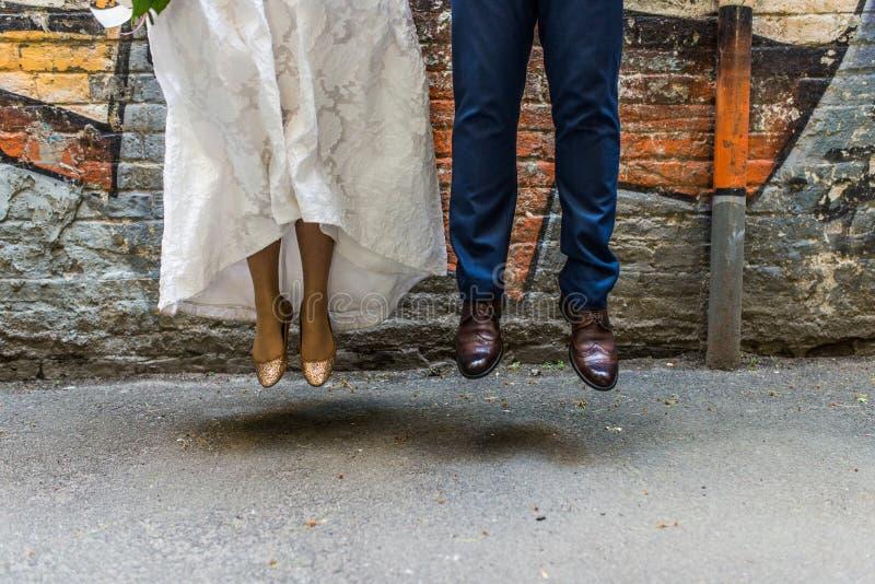 Pieds des nouveaux mariés dans un saut Jeune mariée dans des chaussures d'or sans talons Marié dans des chaussures de Brown photo libre de droits