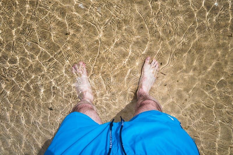 Pieds du ` s d'hommes dans l'eau photos libres de droits