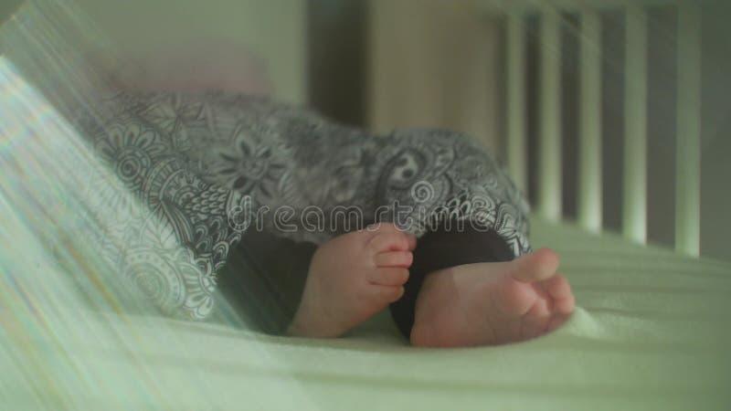 Pieds du ` s de bébé dans le pantalon secouant dans le lit avec la fusée de lentille images stock