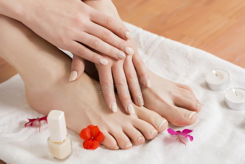 Pieds et mains femelles avec la belles pédicurie et manucure après procédure et fleurs de station thermale et bougie sur la servi photos libres de droits