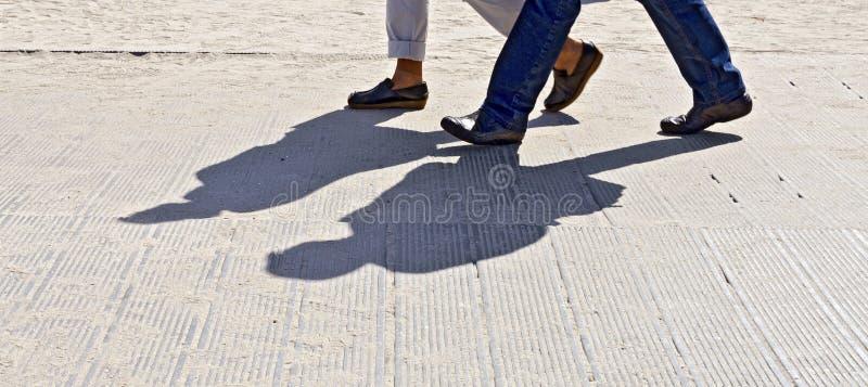 Pieds et ombre de deux marcheurs photographie stock libre de droits